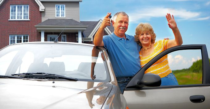 mature couple with their car and home